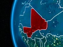 Mali on Earth at night. Space orbit view of Mali highlighted in red on planet Earth at night with visible country borders and city lights. 3D illustration Stock Photography