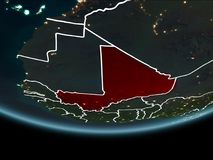 Mali on Earth from space at night. Mali highlighted in red on planet Earth at night with visible borders and city lights. 3D illustration. Elements of this image Stock Photography