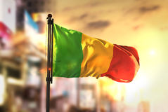 Mali Flag Against City Blurred Background At Sunrise Backlight. Sky Stock Photography