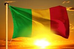 Mali flag weaving on the beautiful orange sunset with clouds background. Mali flag weaving on the beautiful orange sunset background royalty free stock images