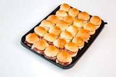 Mali hamburgery na czarnej tacy z białym tłem fotografia stock