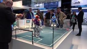 Mali humanoid NAO roboty bawić się piłkę nożną na Messe jarmarku w Hannover, Niemcy ilustracji