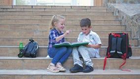 Mali koledzy z klasy siedzi na krokach szkoła z plecakami i przeglądają książkę podczas przerwy w świeżym powietrzu