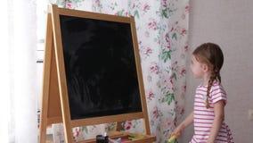 Mali preschool dziewczyny writing listy na blackboard Berbeć dziewczyny mienia rysunek i kreda zbiory