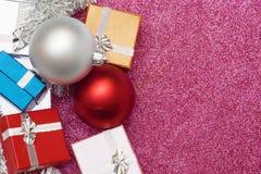 Mali pudełka dla prezenta i dwa bożych narodzeń balowych na czerwieni Zdjęcia Stock