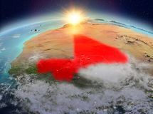 Mali from space in sunrise. Satellite view of Mali highlighted in red on planet Earth with clouds during sunrise. 3D illustration. Elements of this image Stock Photo