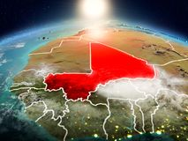 Mali in sunrise from orbit. Sunrise above Mali highlighted in red on model of planet Earth in space with visible country borders. 3D illustration. Elements of Royalty Free Stock Photo