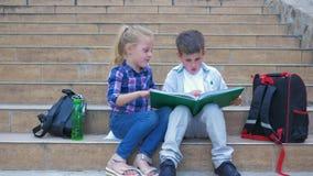 Mali ucznie siedzi na krokach i leafing przez książki podczas recesji szkoła z plecakami w na wolnym powietrzu