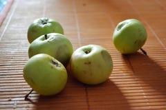 Mali zieleni jabłka na stole z pomarańczowym tablecloth Zdjęcie Royalty Free