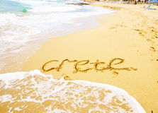 Malia beach, Crete, Greece. Sandy beach with sea waves and  word Crete, Greece Royalty Free Stock Images