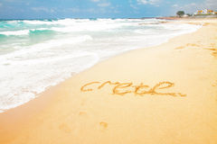 Malia beach, Crete, Greece. Sandy beach with sea waves and word Crete, Greece Stock Images