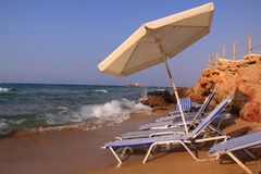 Malia beach crete. Sun beds and umbrella at the sand beach of the greek village malia, crete Royalty Free Stock Photos