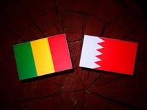 Malian flag with Bahraini flag on a tree stump  Stock Image