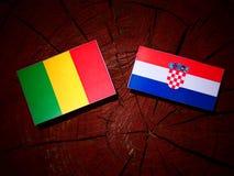 Malian flag with Croatian flag on a tree stump royalty free stock image