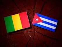 Malian flag with Cuban flag on a tree stump isolated. Malian flag with Cuban flag on a tree stump royalty free stock photos