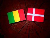 Malian flag with Danish flag on a tree stump isolated. Malian flag with Danish flag on a tree stump stock photos
