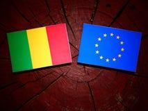 Malian flag with EU flag on a tree stump isolated. Malian flag with EU flag on a tree stump royalty free stock photos