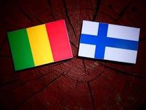 Malian flag with Finnish flag on a tree stump isolated. Malian flag with Finnish flag on a tree stump royalty free stock photo