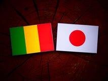 Malian flag with Japanese flag on a tree stump isolated. Malian flag with Japanese flag on a tree stump stock image