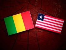 Malian flag with Liberian flag on a tree stump isolated. Malian flag with Liberian flag on a tree stump stock image