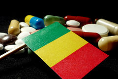 Malian flag with lot of medical pills isolated on black background stock photography