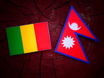Malian flag with Nepali flag on a tree stump isolated. Malian flag with Nepali flag on a tree stump Stock Photography