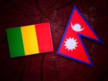 Malian flag with Nepali flag on a tree stump isolated. Malian flag with Nepali flag on a tree stump stock photography