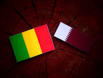 Malian flag with Qatari flag on a tree stump isolated. Malian flag with Qatari flag on a tree stump Royalty Free Stock Photography