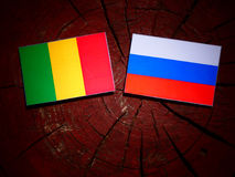 Malian flag with Russian flag on a tree stump royalty free stock photos