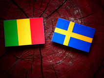 Malian flag with Swedish flag on a tree stump stock photos
