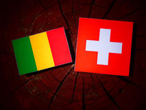 Malian flag with Swiss flag on a tree stump stock photos