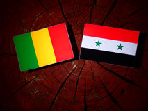 Malian flag with Syrian flag on a tree stump isolated Stock Photo
