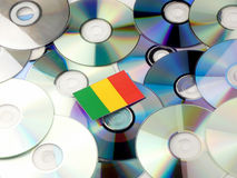 Malian flag on top of CD and DVD pile  on white. Malian flag on top of CD and DVD pile Royalty Free Stock Image