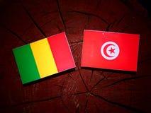 Malian flag with Tunisian flag on a tree stump isolated. Malian flag with Tunisian flag on a tree stump stock photo