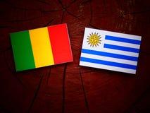 Malian flag with Uruguaian flag on a tree stump isolated. Malian flag with Uruguaian flag on a tree stump royalty free stock photography