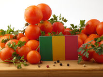 Malian flag on a wooden panel with tomatoes isolated on a white. Background royalty free stock photos