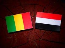 Malian flag with Yemeni flag on a tree stump stock photography