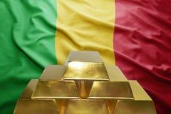 Malian gold reserves. Shining golden bullions on the malian flag background stock photos