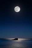 Malibu Beachscape Moon. Leo Carillo Beach just outside of Malibu.  The moon shines over a rock in the ocean, reflecting in the water Stock Images
