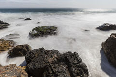Malibu California Pacific Ocean Rocks with Motion Blur. Malibu coast rocks with motion blur water at Point Dume near Los Angeles California Stock Photos