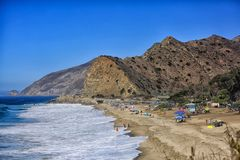Malibu coastline. Beach with sand mountains umbrellas swimmers and Pacific Ocean in Malibu California Stock Images