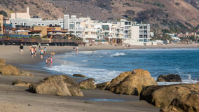 Malibu Coastline. Looking south from the pier down the beach lining the coast at Malibu, California. With luxury seaside homes and beach visitors Royalty Free Stock Photo