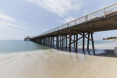 Malibu Pier with Motion Blur Pacific Water. Malibu Pier beach with motion blur pacific ocean water near Los Angeles in Southern California Stock Photo