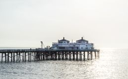 Malibu pier in California on a foggy morning. Malibu pier and shoreline in California with early morning fog and reflection of sunlight on the ocean Stock Photography