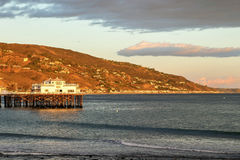 Malibu Pier. Sun is about to set at Malibu Pier casting warm lights to the hills, Malibu California Stock Photos