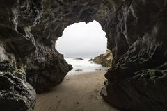 Malibu Sea Cave in Southern California. Sandy floor sea cave with motion blur water at Leo Carrillo State Beach in Malibu, California Royalty Free Stock Images