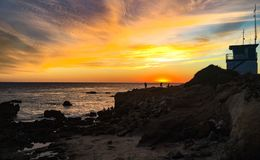Malibu Sunset. Beautiful beach sunset in Malibu, California with rocky cliffs and ocean waves Stock Image