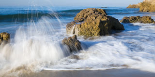Malibu White Water. This is an image shot in the early morning of wild surf pounding against a rocky and secluded beach in Malibu, California Stock Images