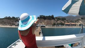 Malibu woman panorama. Happy girl on top of Malibu Pier in California West Coast, United States. Caucasian girl pointing at popular Carbon Beach in summer stock video