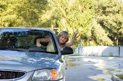 Malicious girl driver. The malicious girl-driver threatens with a hand Royalty Free Stock Photography